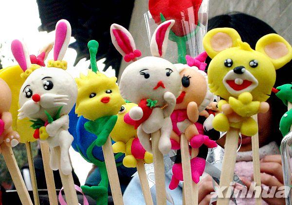 在一个庙会的面塑工艺品展台上,两只小白兔和其他小动物